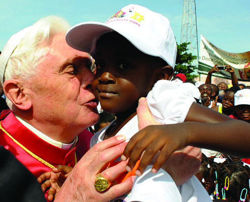 Pope Benedict XVI kisses a child during his visit in Luanda March 21, 2009.    REUTERS/Osservatore Romano/Pool   (ANGOLA RELIGION SOCIETY IMAGE OF THE DAY TOP PICTURE)